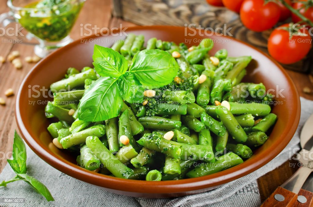 Green beans with pesto and pine nuts stock photo