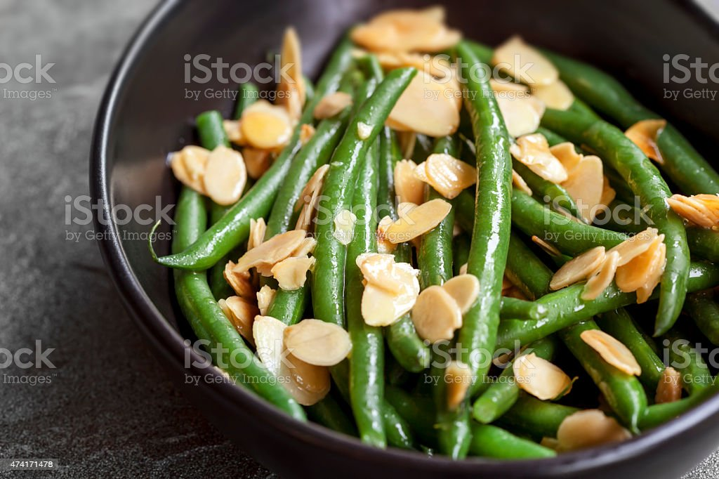 Green Beans with Toasted Almonds in Black Bowl stock photo
