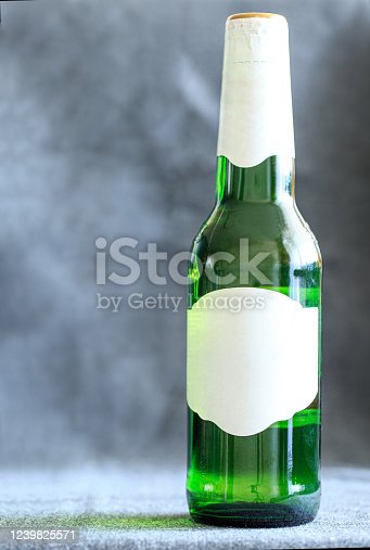 1073474208 istock photo Green beer bottle with a white label on a fabric background. 1239825571