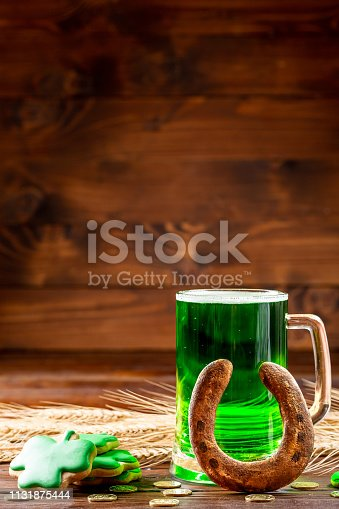 1124676977 istock photo Green beer in a glass mug with gingerbread clover, horseshoe and gold coins on a rustic wooden surface. Festive background for St. Patrick's day with wheat ears. Free space 1131875444