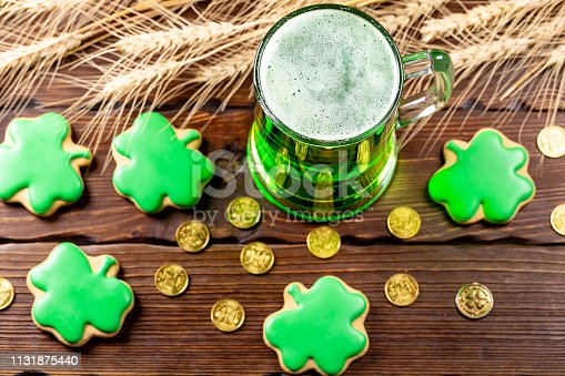 1124676977 istock photo Green beer in a glass mug with gingerbread clover, horseshoe, wheat spike and gold coins on a rustic wooden surface. Festive background for St. Patrick's day. 1131875440