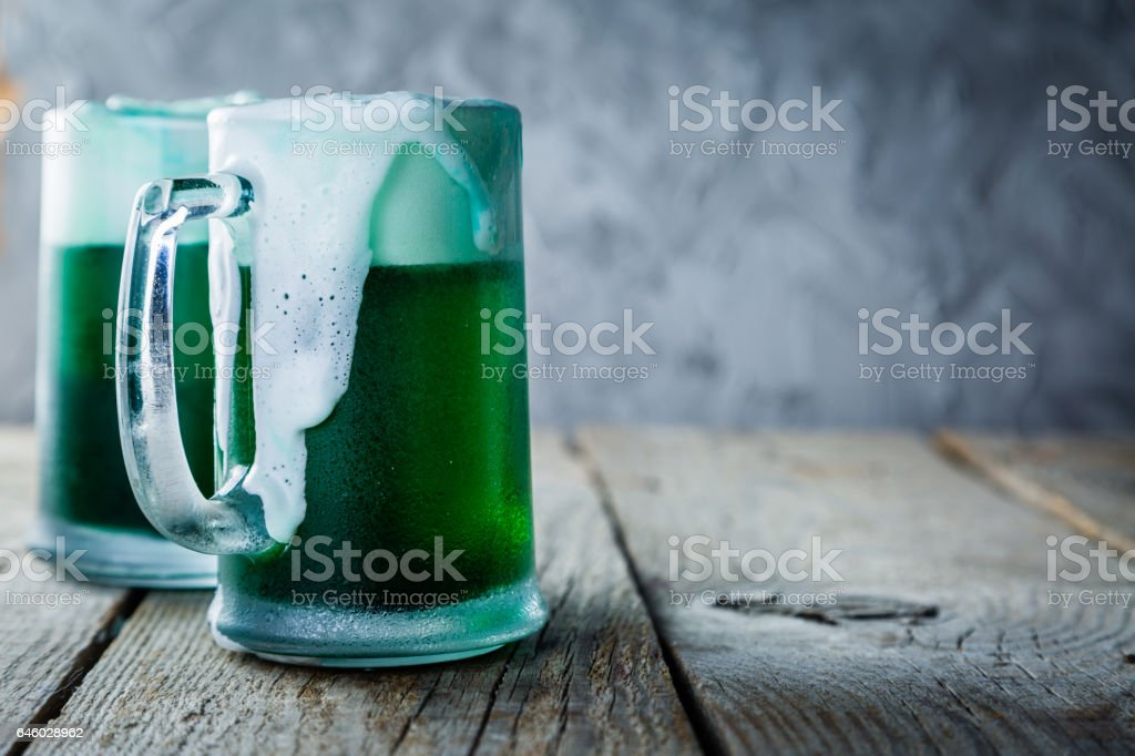 Green beer in mugs on rustic wood background stock photo