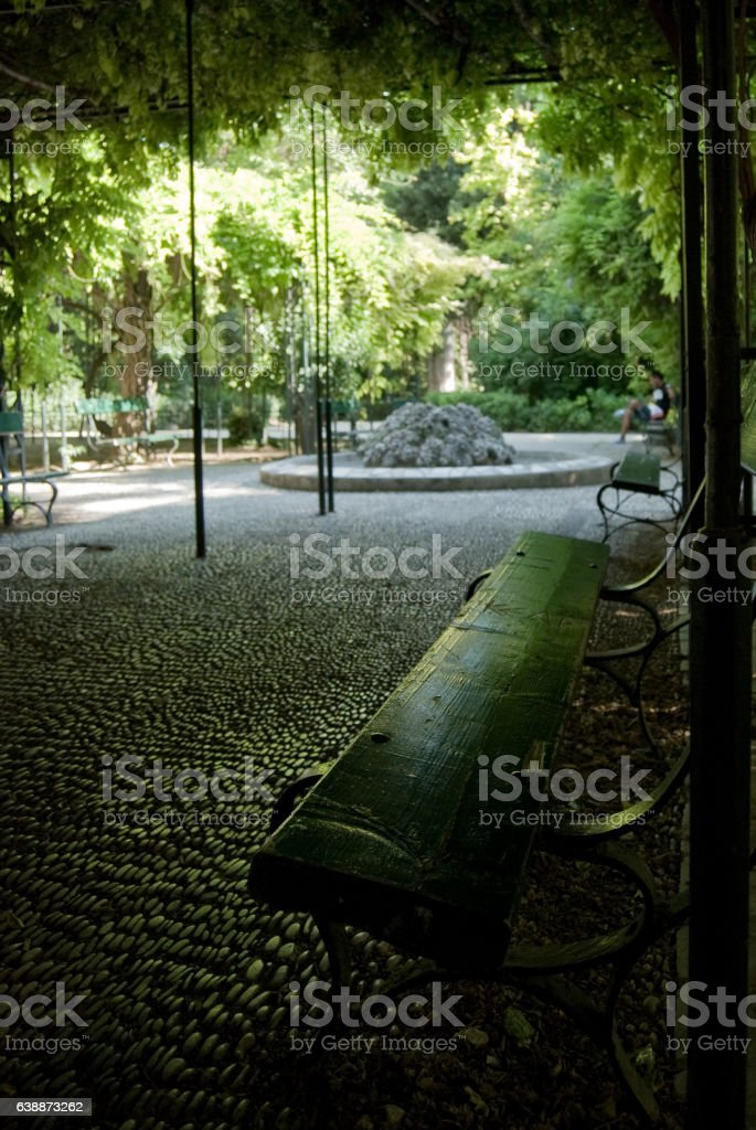 Green bench in a lush public park, Athens stock photo