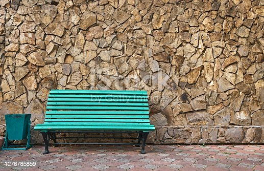Green bench stands against a wall of wild stone. The walls are tiled with wild stone tiles. Rest after a walk. Close up, with copy space.