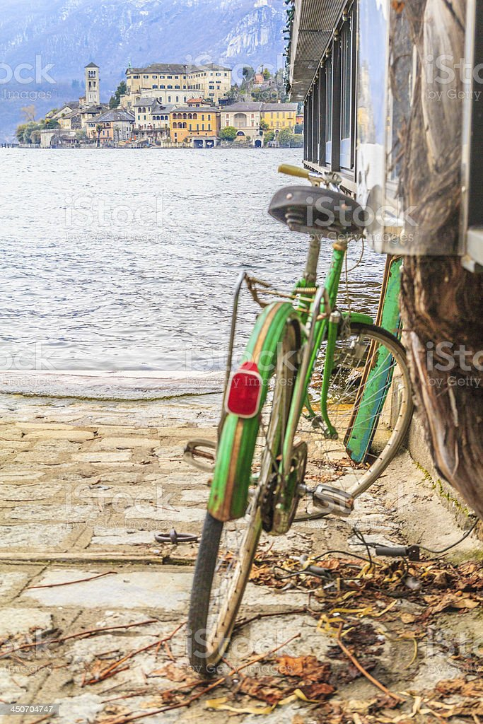 Green bicycle leaning against wall at the italian lake. royalty-free stock photo