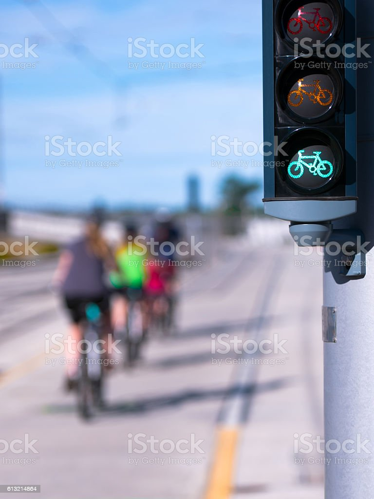 Green Bike traffic lights and riding cyclists stock photo