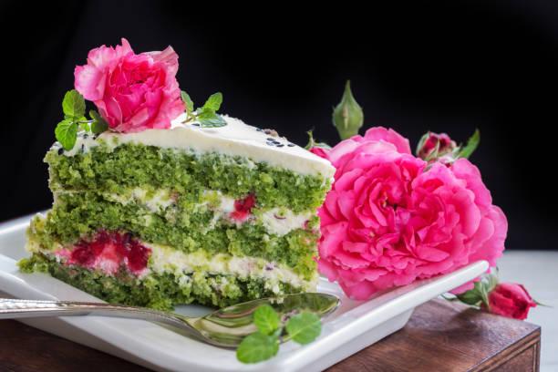 grüne keks-kuchen mit quark-creme und ruspberries. spinat-torte mit rosenblüten - grüntee kuchen stock-fotos und bilder