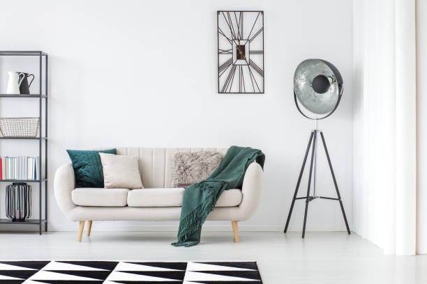 grüne decke auf beige sofa - uhrenhalter stock-fotos und bilder