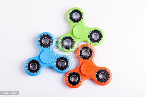 Green, blue and orange fidget spinner stress relieving toy on white background
