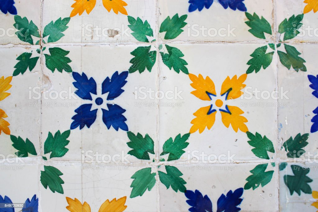 Green, blue and yellow leaf-patterned tiles on a building in Lisbon stock photo