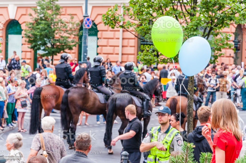 Green blue balloons on foreground and armed mounted police forces riding at the end of Pride parade on Gedimino street on the background stock photo