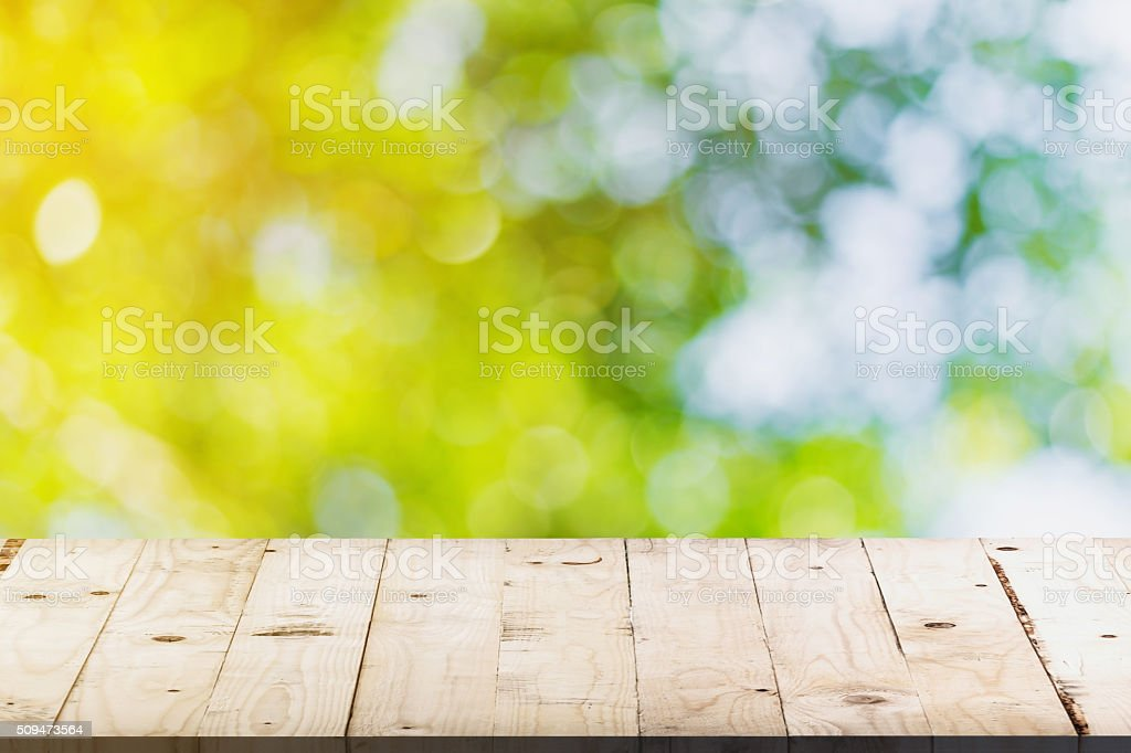 green bokeh and soft light in garden and wood table stock photo