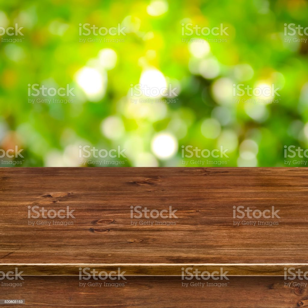 Green bokeh lights background with wooden table stock photo