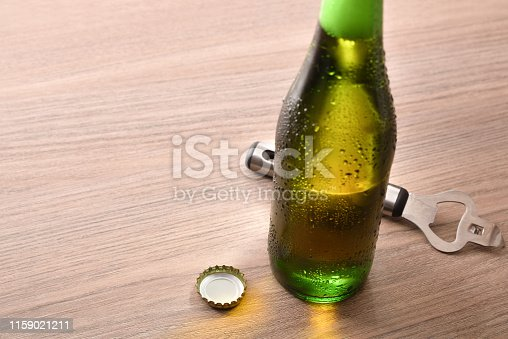 Green bottle with alcoholic beverage on wood table elevated. Horizontal composition. Elevated view.