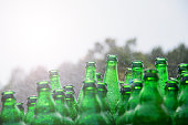 Closeup photo of a big pile of green, empty, sprinkled bottles.