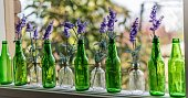 A row of green bottles tied together in a window with purple lavender flowers in each one