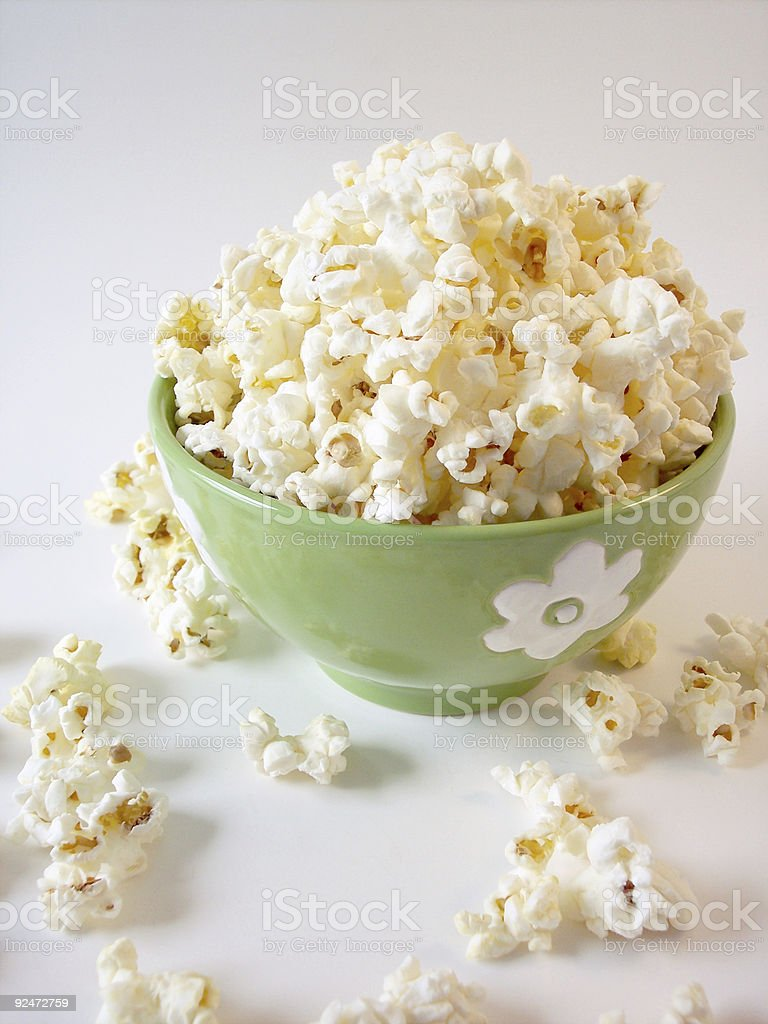 Green bowl with a flower decoration filled with popcorn royalty-free stock photo