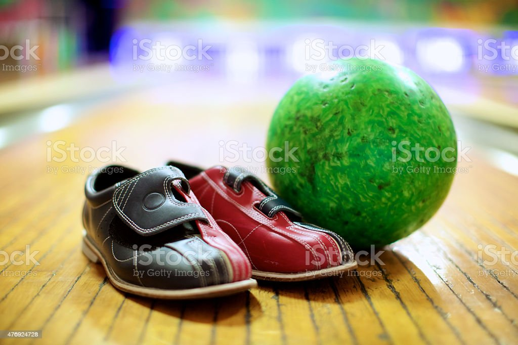 Green bowling ball and colorful bowling shoes stock photo