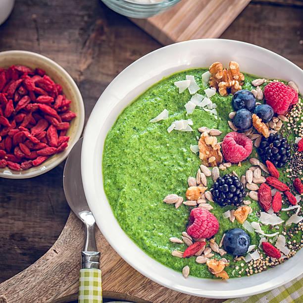 grün frühstück-smoothie in schüssel mit superfoods auf der oberseite - quinoa superfood stock-fotos und bilder