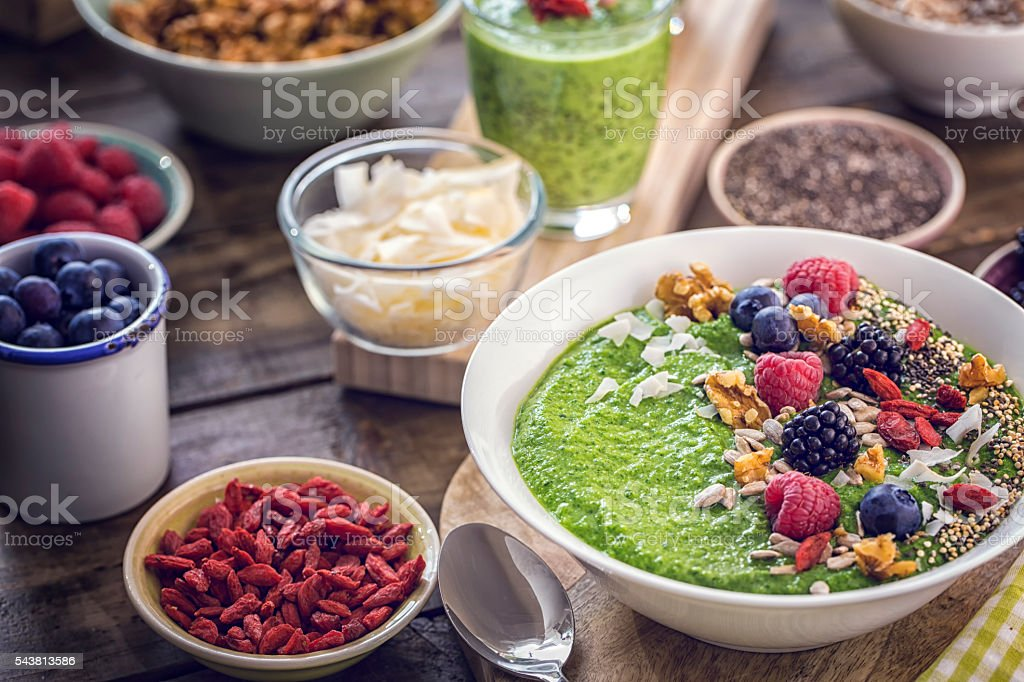 Green Breakfast Smoothie in Bowl with Superfoods on Top Green breakfast smoothie in bowl with superfoods like chia, quinoa, goji, fresh berries and sunflower seeds. Antioxidant Stock Photo