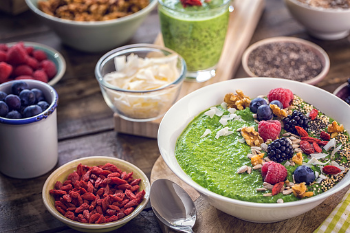 Green Breakfast Smoothie In Bowl With Superfoods On Top Stock Photo - Download Image Now