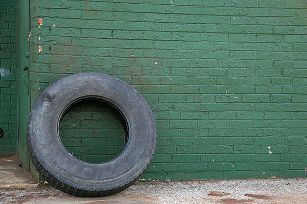 Green brick wall with tire