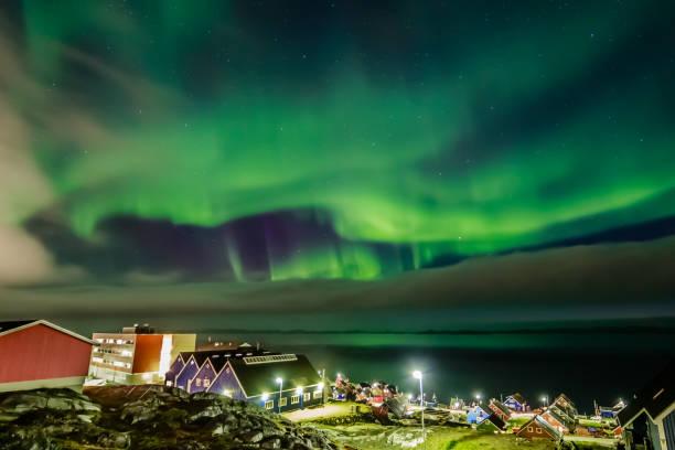 Grün leuchtend Nordlicht versteckt durch die Wolken über dem Inuit-Dorf an der Förde, Stadt Nuuk, Grönland – Foto