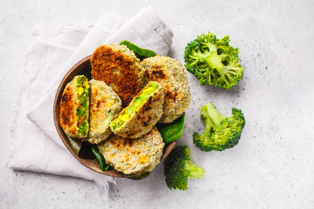 Green broccoli burgers in coconut shell dish on white background, top view. stock photo