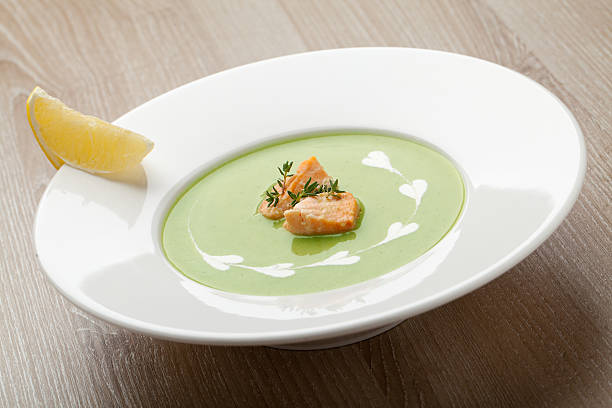 Green broccoli cream soup puree with filleted salmon  and  lemon stock photo