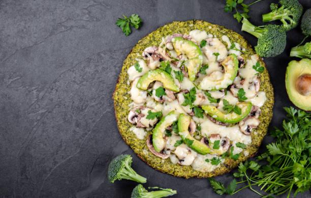 grüner brokkoli-teig krustenpizza mit avocado, käse. low carbs, ketogene diät vegane vegetarische pizza auf schiefer hintergrund top-ansicht - low carb pizzateig stock-fotos und bilder