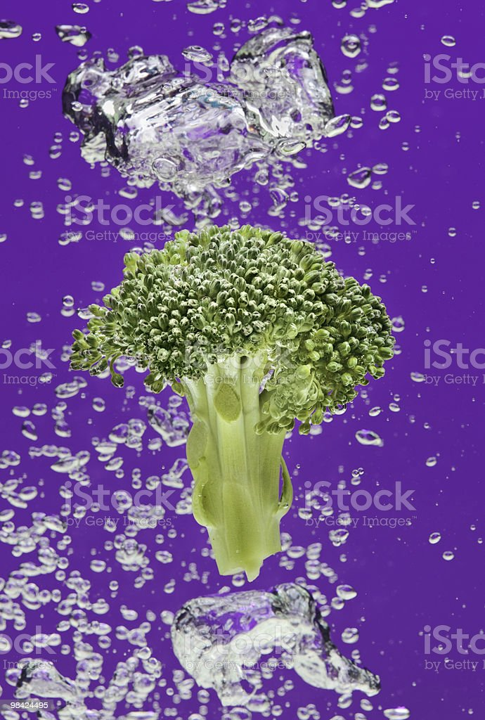 Green broccoli falling in water with air bubbles royalty-free stock photo