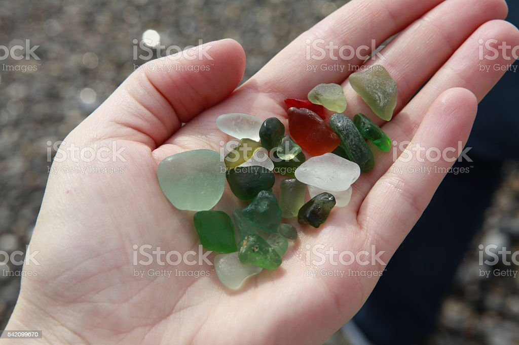 Green, brown, white seaglass in the hand stock photo