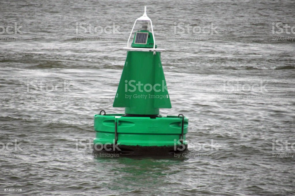 Green buoy in the Nieuwe maas river in Rotterdam stock photo