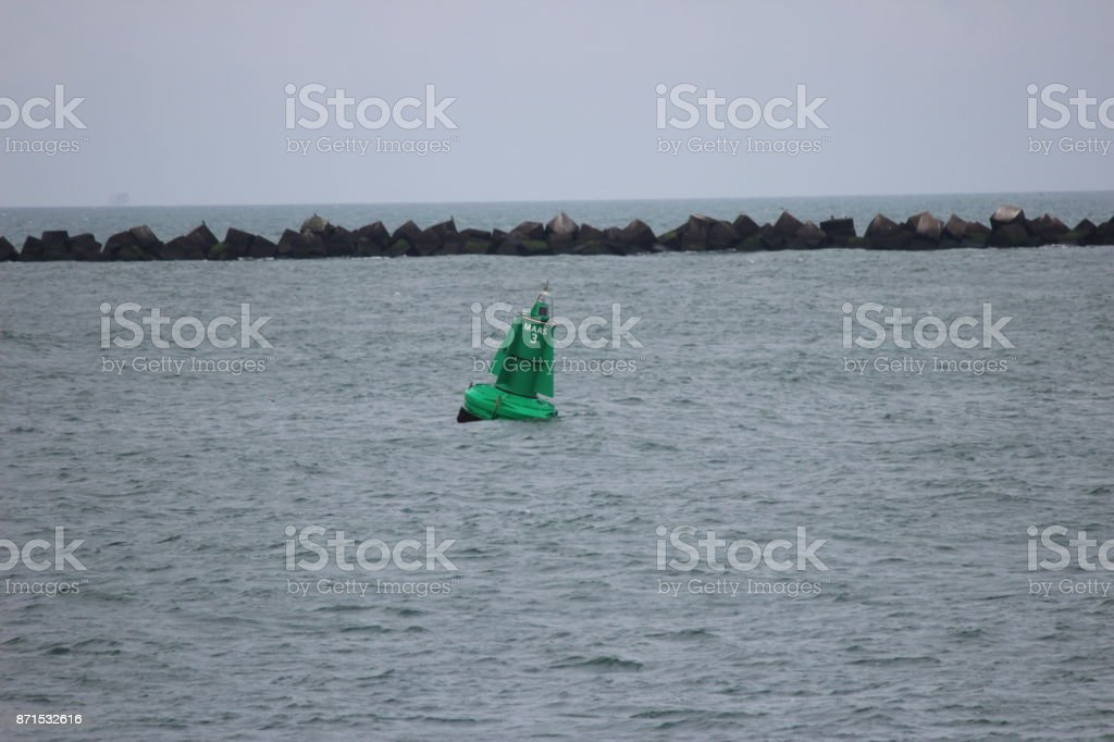Green buoy in the river maas to give the correct direction to the watercourse stock photo
