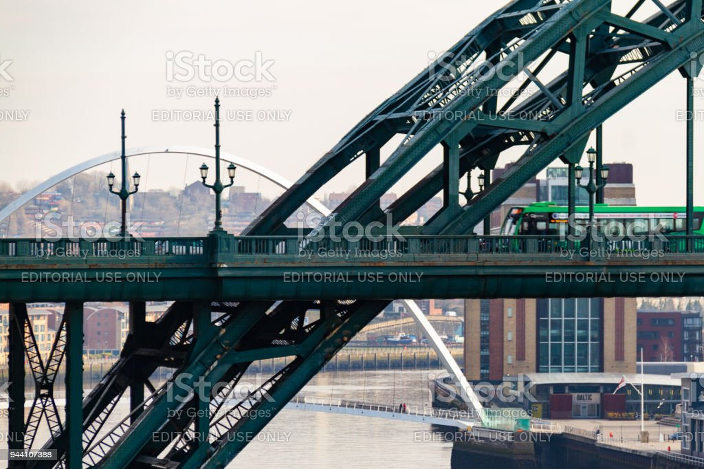 Green bus crossing the Tyne Bridge and Millennium Bridge in the distance at Newcastle Quayside on a cloudy day stock photo