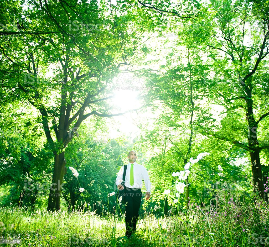 Green Businessman walking in a Woodland royalty-free stock photo