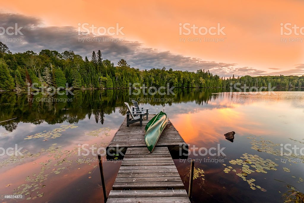 Green Canoe and Chairs on a Dock at Sunset stock photo