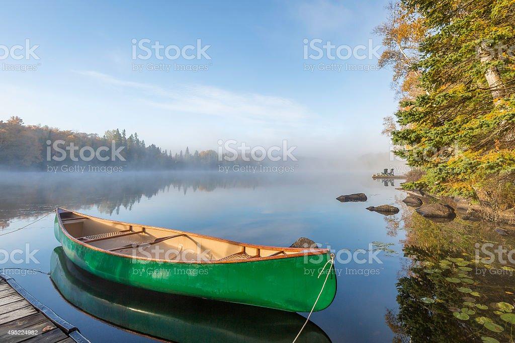 Green Canoe Tied to Dock stock photo