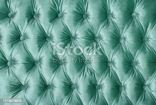 Pastel teal green velvet capitone textile background, retro Chesterfield style checkered soft tufted fabric furniture diamond pattern decoration with buttons, close up