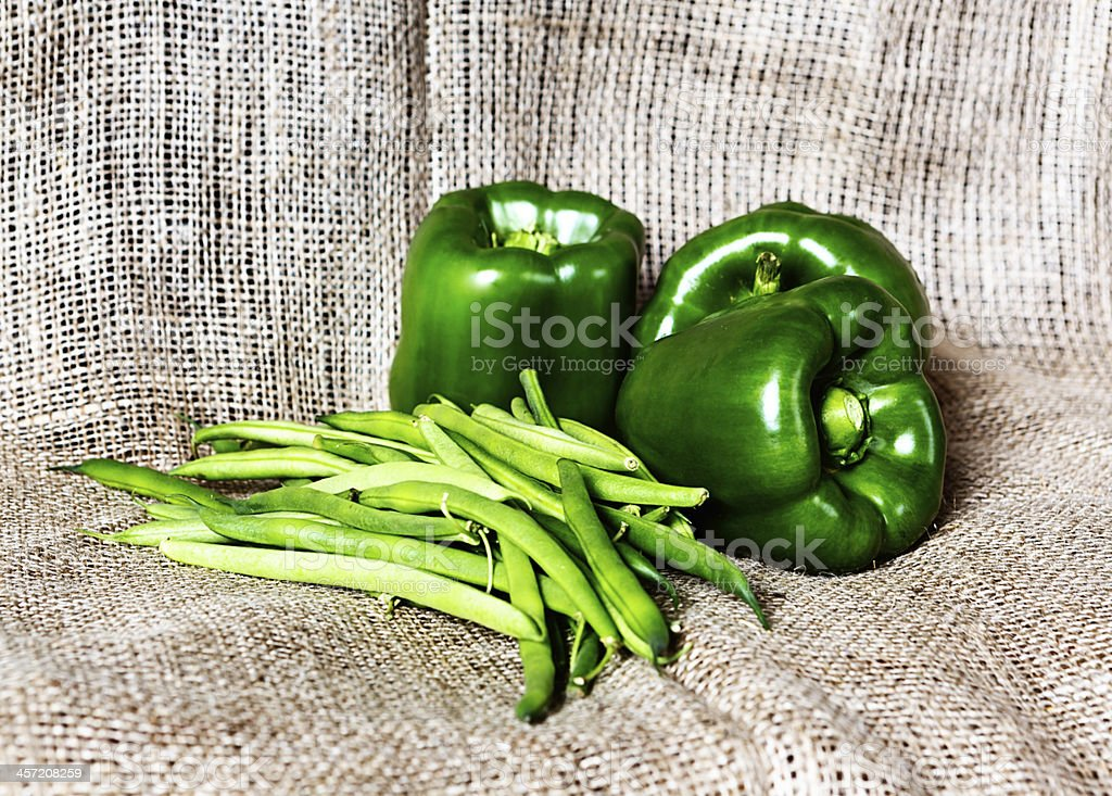 Green capsicums and string beans on burlap royalty-free stock photo