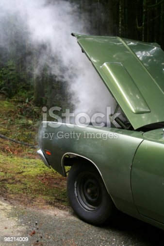 A car steams from overheating on the side of the road.