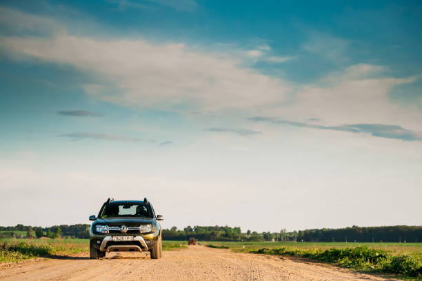 Green Car Renault Duster Suv Parked On Field Country Road. stock photo