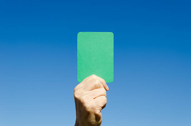 Green card against blue sky A green card in the hand against blue sky. In certain games, the card is used by the judge to admire the player who plays fair. green card stock pictures, royalty-free photos & images