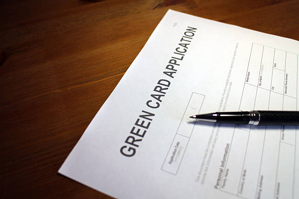 Green Card Application Document Someone filling out Green Card Application Form. green card stock pictures, royalty-free photos & images