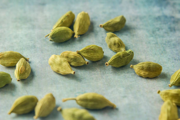 green cardamom Close up green cardamom seeds in wooden spoon cardamom stock pictures, royalty-free photos & images