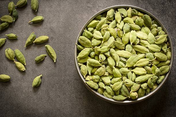 green cardamom pods in  steel bowl green cardamom pods in steel bowl with wooden background top view flat lay cardamom stock pictures, royalty-free photos & images