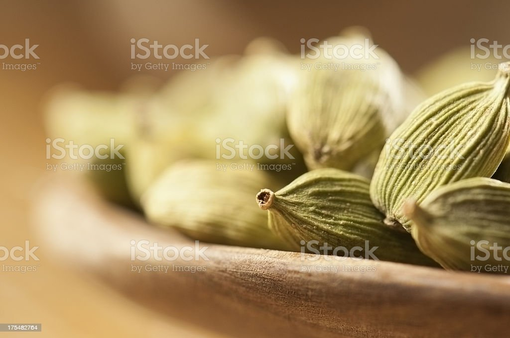 Green cardamom seeds in small wooden bowls stock photo