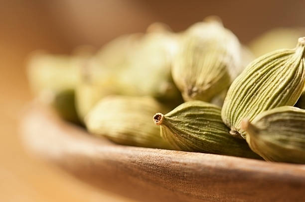 Green cardamom seeds in small wooden bowls Cardamom pods in a small wooden bowl cardamom stock pictures, royalty-free photos & images