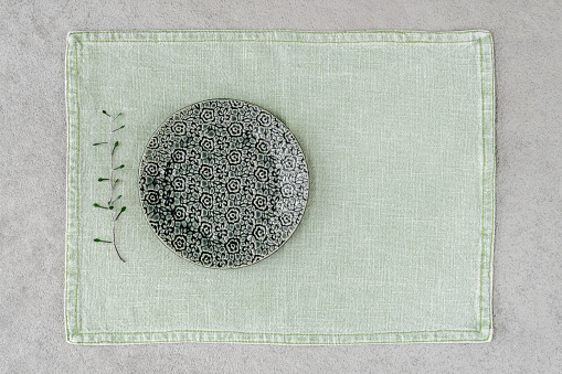 Green ceramic plate on linen placemat