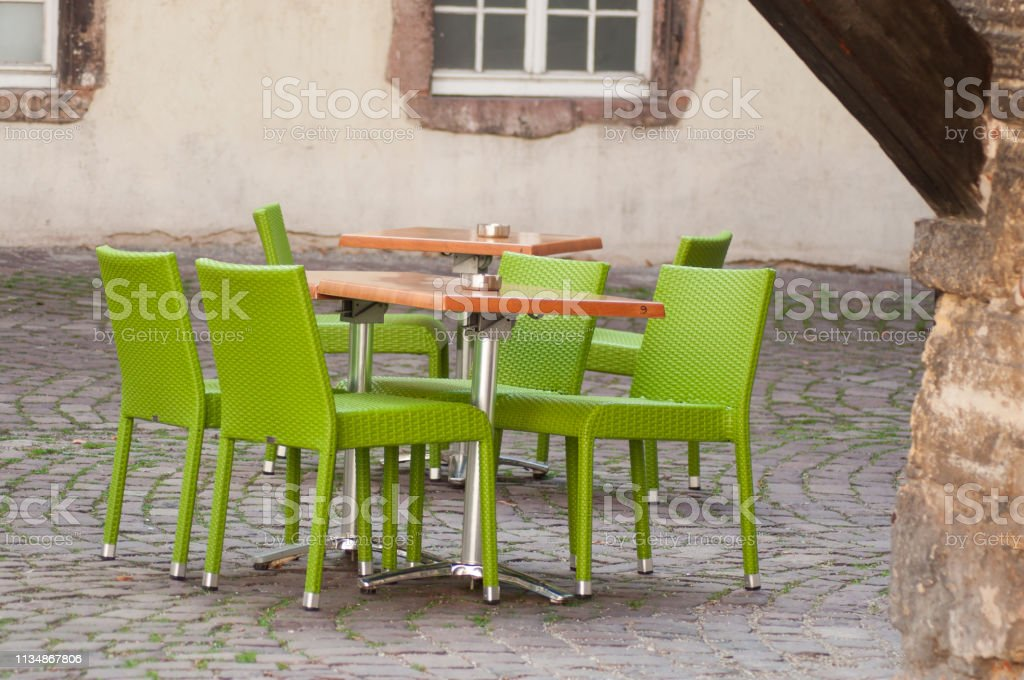 closeup of green chairs at the terrace of the restaurant in the street